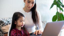 parent help daughter on laptop