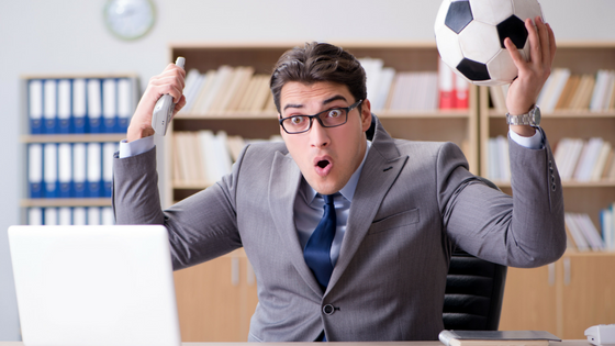man-cheering-in-business-suit-holding-soccer-ball-while-at-work