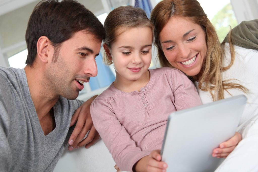 child-holding-tablet-while-mom-and-dad-watch
